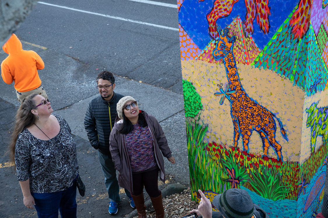 three people get up close to look at the mural paintings
