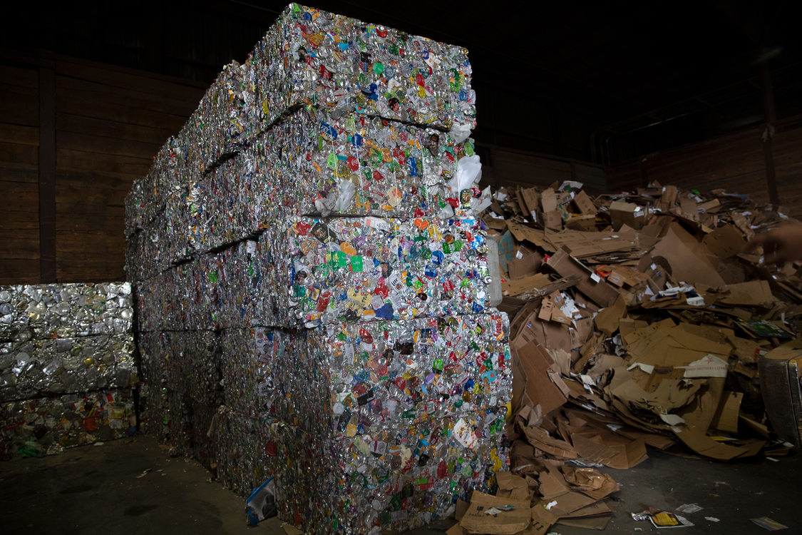 stacked bales of separated aluminum and tin stand next to a pile of lose cardboard