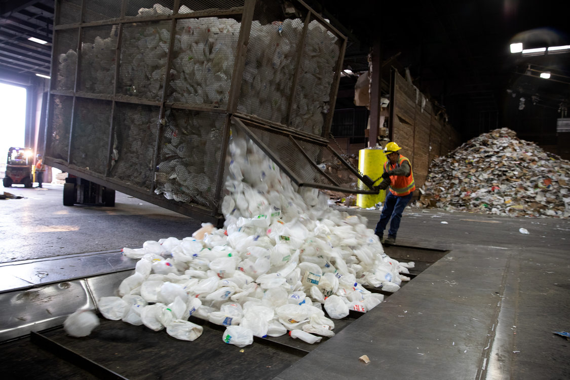 a worker opens a huge bin of plastic milk jugs onto a conveyor belt