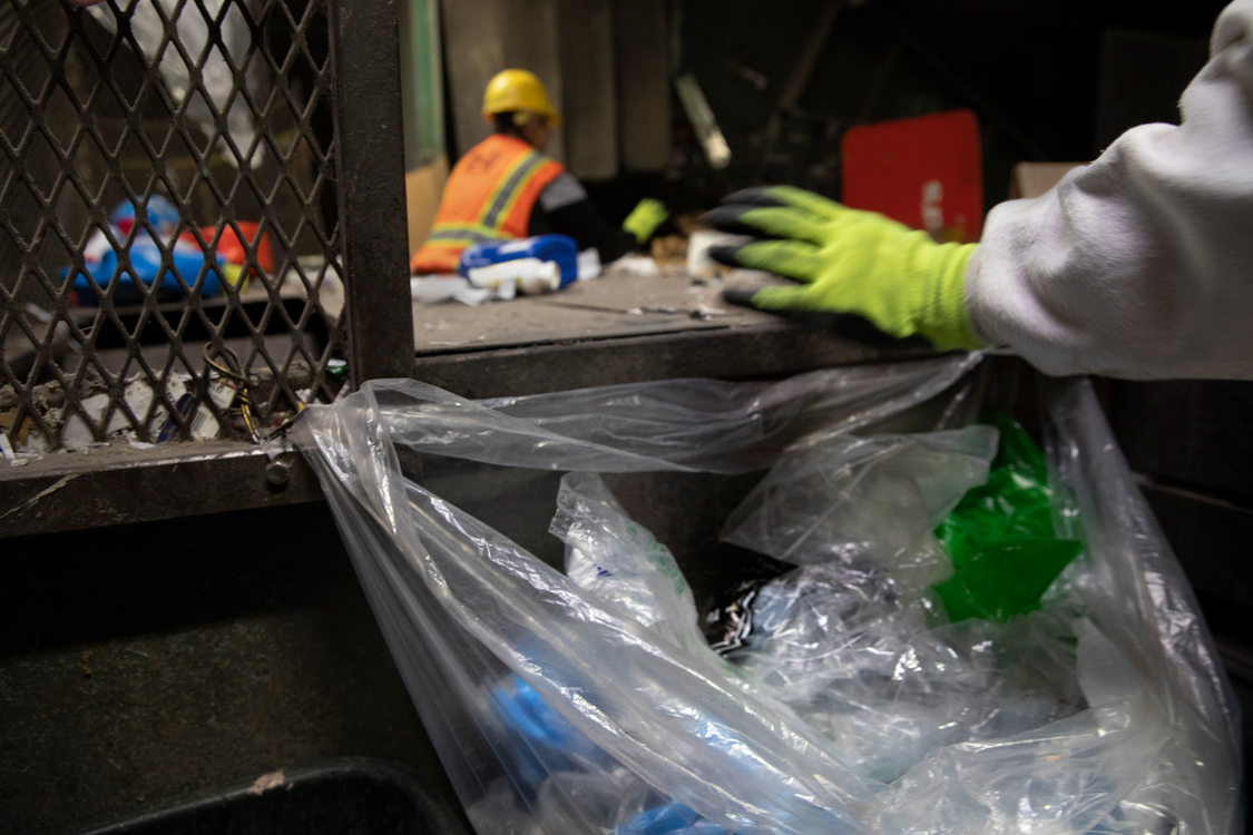 workers on the sorting line pull off plastic bags