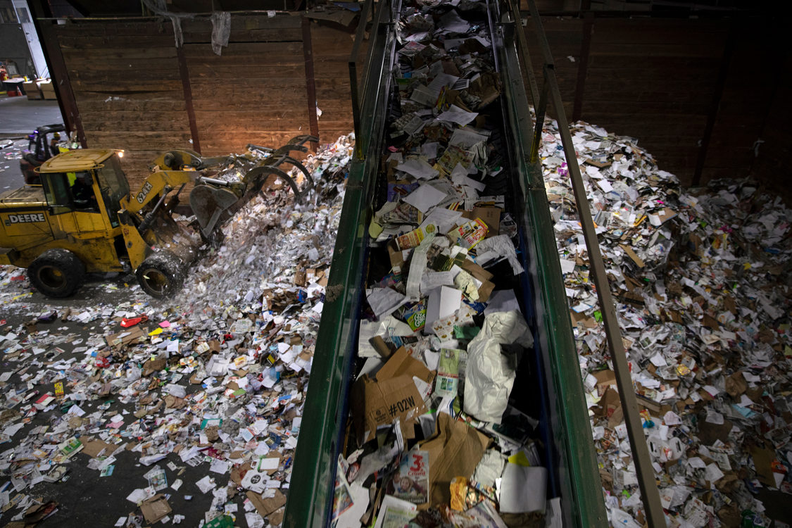an elevated conveyor belt carries paper and dumps it into a huge pile on the floor. A tractor worked to move the pile.