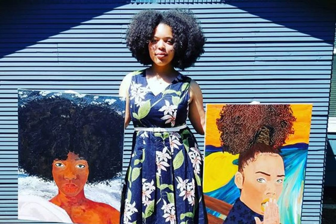 a woman stands tall on a sidewalk holding two of her paintings