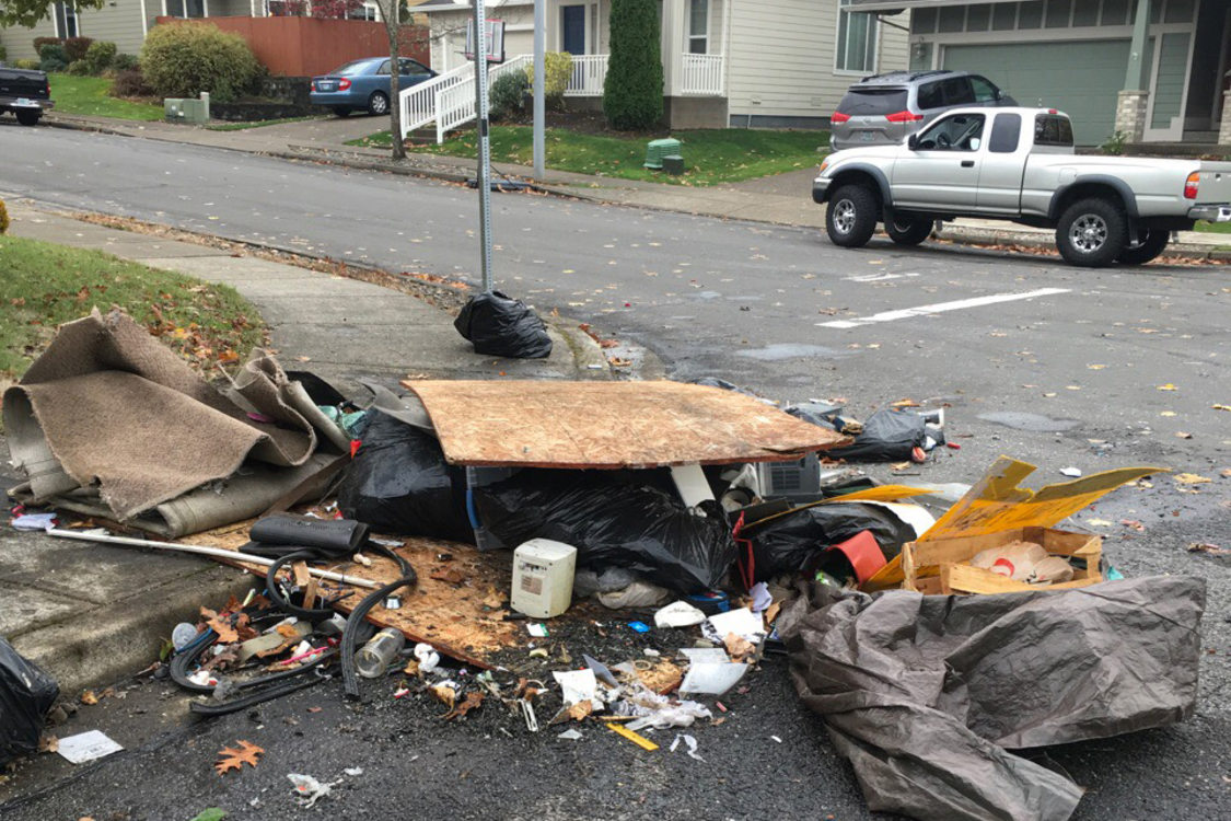 Trash and wood debris are strewn across a city corner