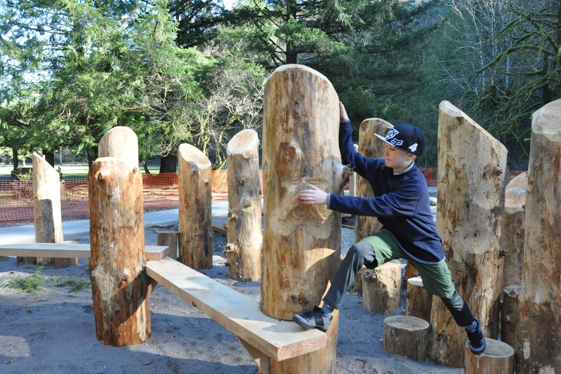 A boy plays on logs sunk in sand at the nature play area at Oxbow Regional Park