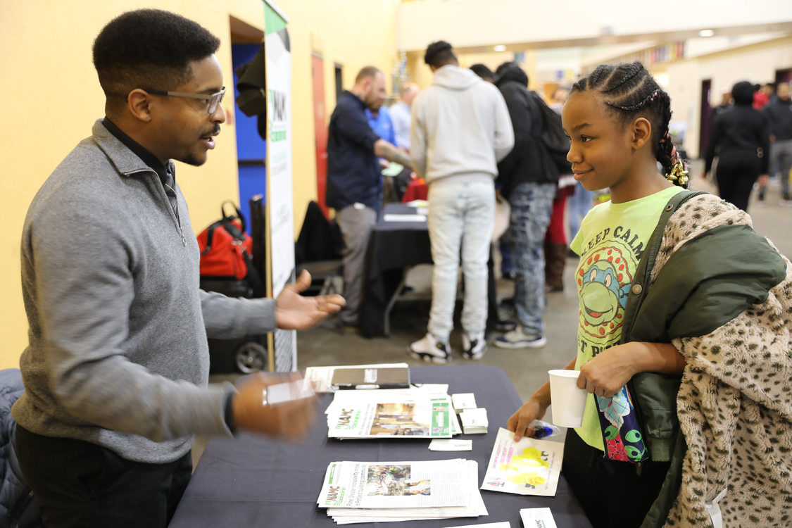 man talks to student at SEI trades fair