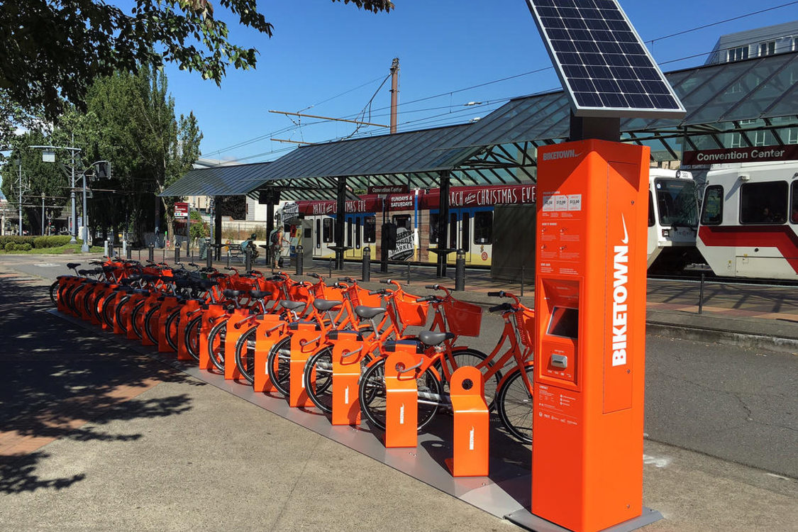 A Biketown station with the MAX light rail train in the background
