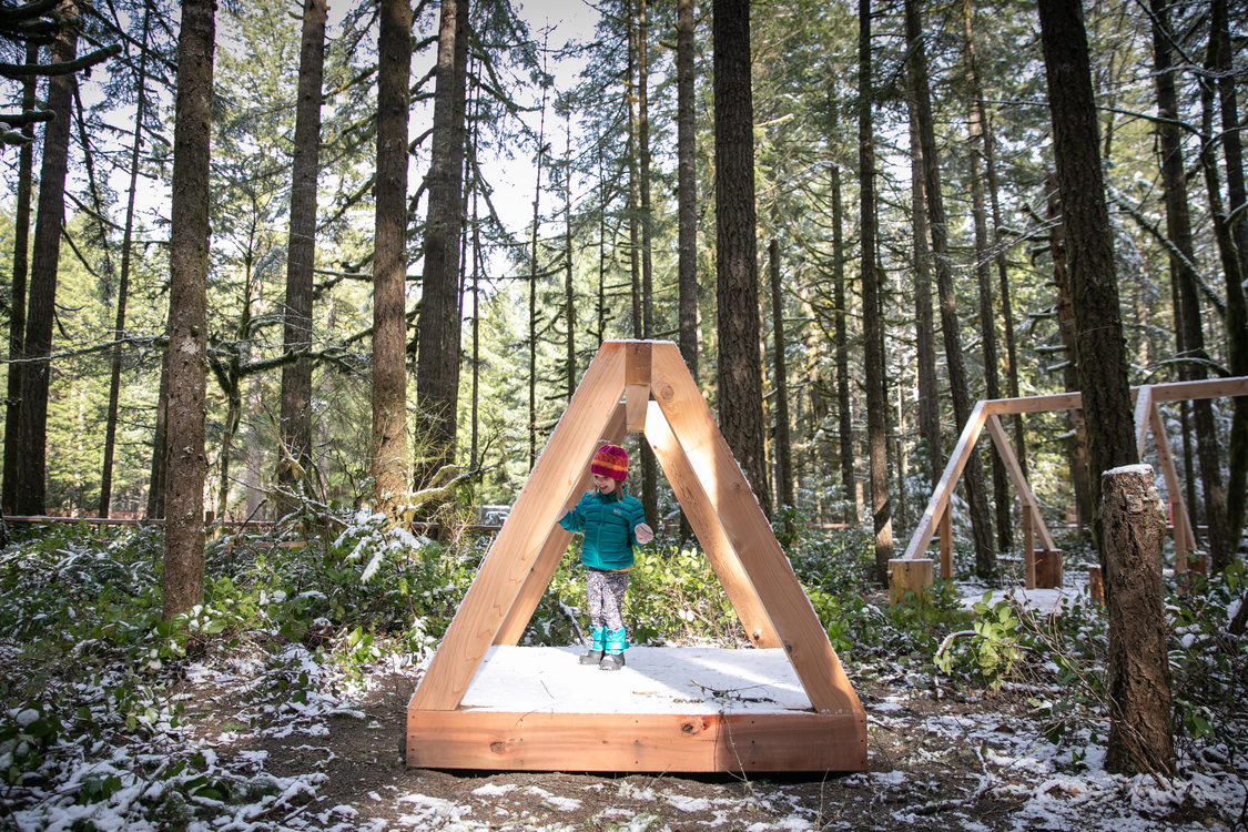 girl in winter clothes stands in triangular nature play structure in woods