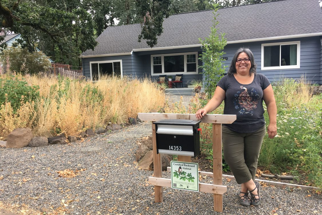 A person stands in front of their home, smiling, their backyard habitat certification sign is displayed under their mailbox and native plant habitat is visible in their front yard.