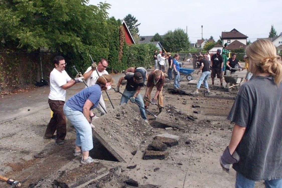 Several adults weilding crowbars or shovels work together to lift large panels of concrete. In the background are more volunteers some doing the same, others loading wheelbarrows and several homes.