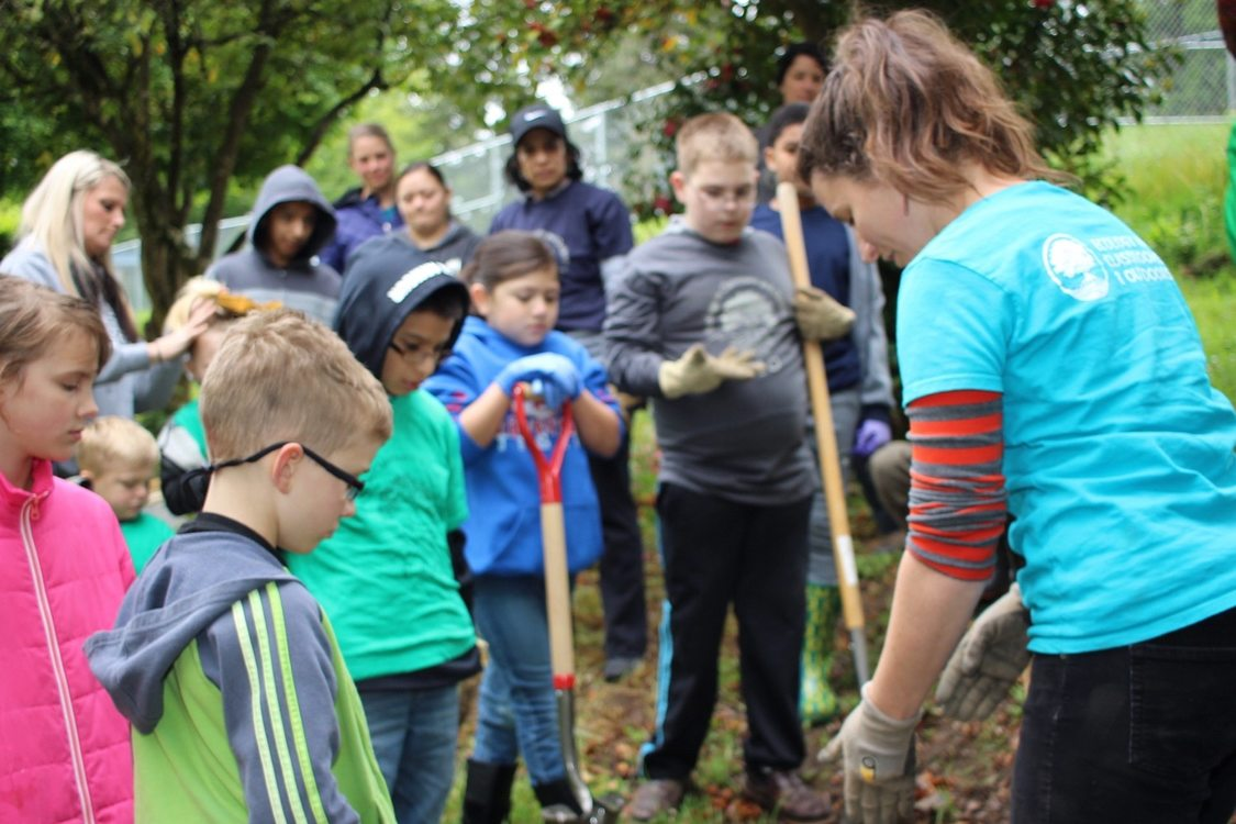 Several elementary age students watch closely, shovels in hand, as a nature educator points their attention to the ground. There are trees and adult observers in the background.