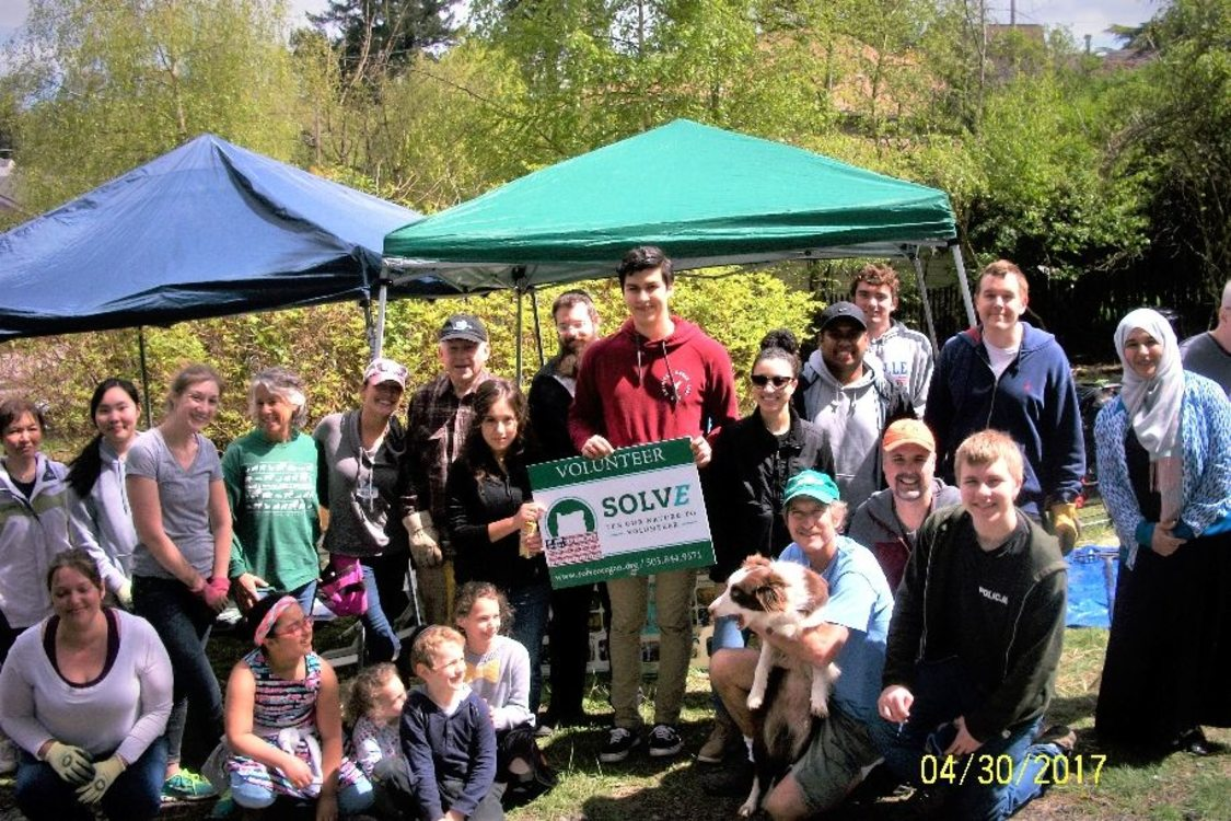 A large group of people ranging in age pose and smile holding a 'Volunteer with SOLVE' sign. There are pop up tents and trees in the background.