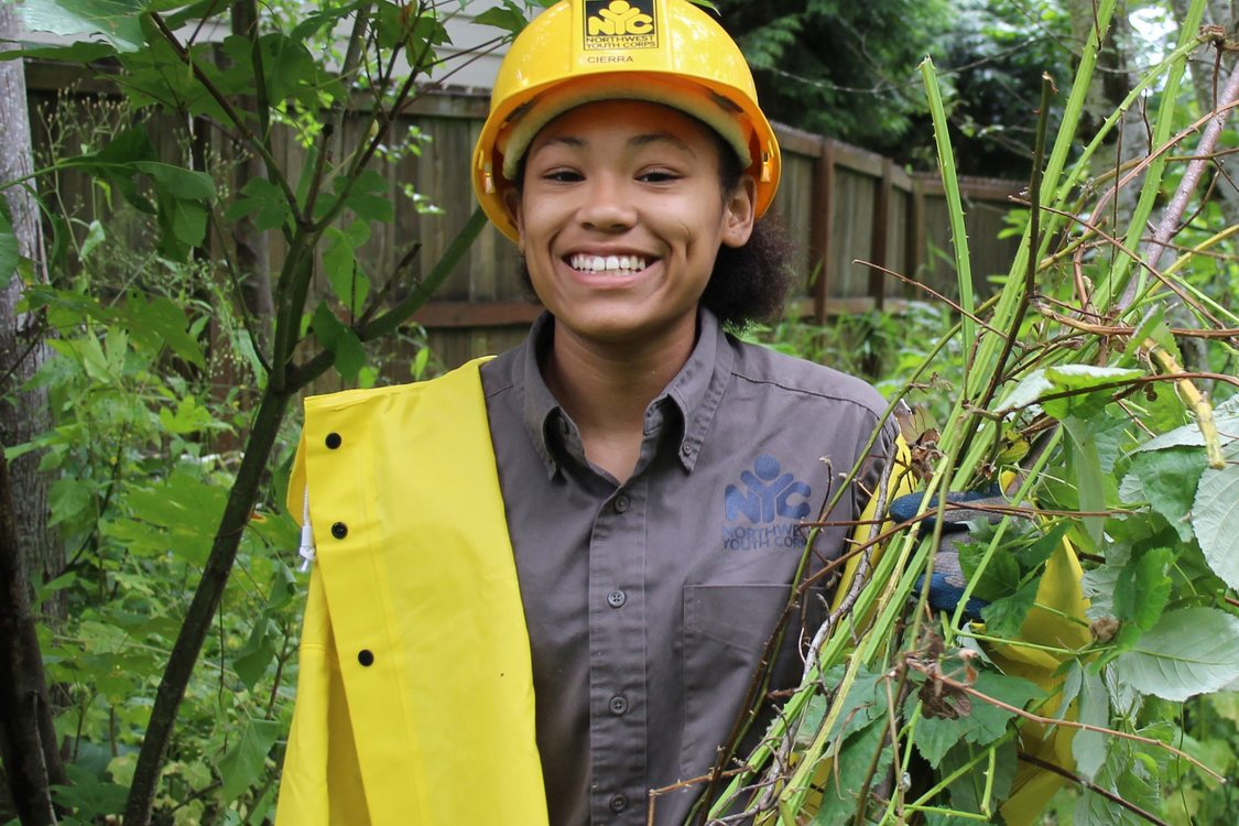 A youth wearing NW Youth Corps shirt, raincoat and hardhat smiles widely holding a pile of cut Himilayan Blackberry in their gloved hands. Greenery and a wood fence are visible in the background.