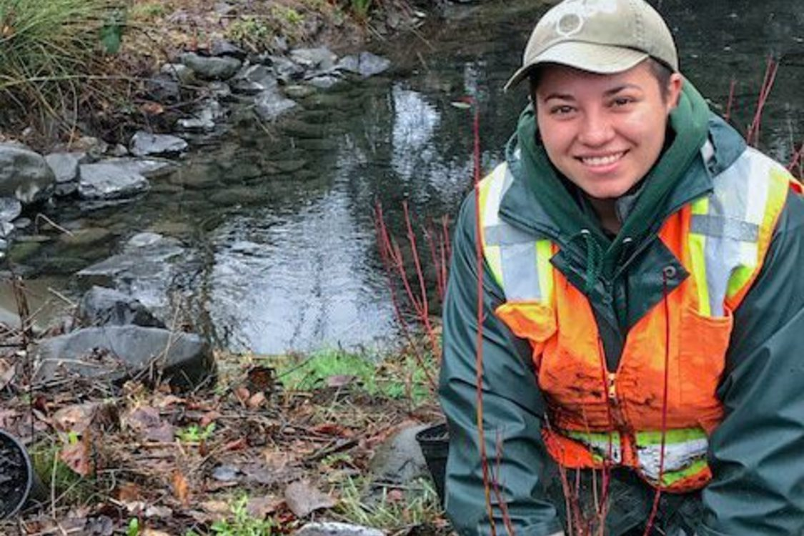A person wearing rain gear, work gloves and an orange safety vest kneels smiling in front a new planting, a small shovel at their side. Behind them is a calm waterway.