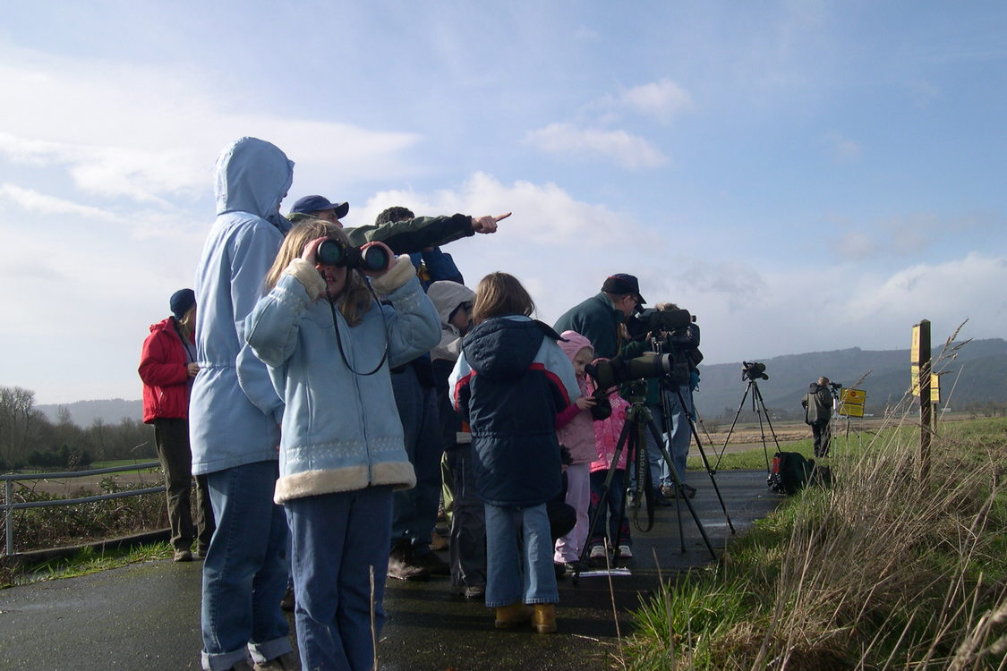 Raptor road trip participant using binoculars in group