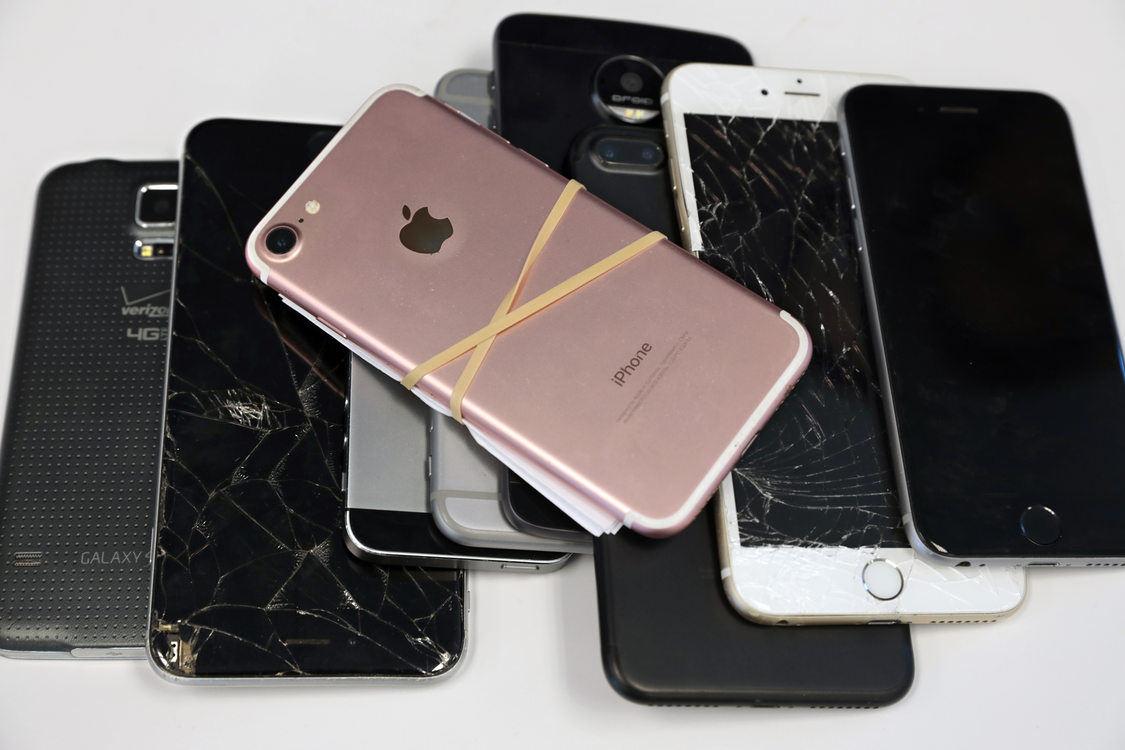 a pile of used and broken smart phones