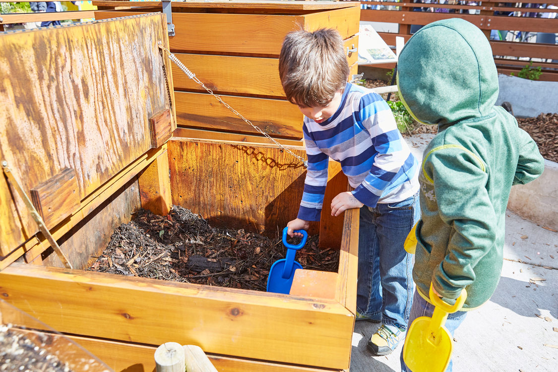 2 children digging in compost bin at zoo wildlife garden