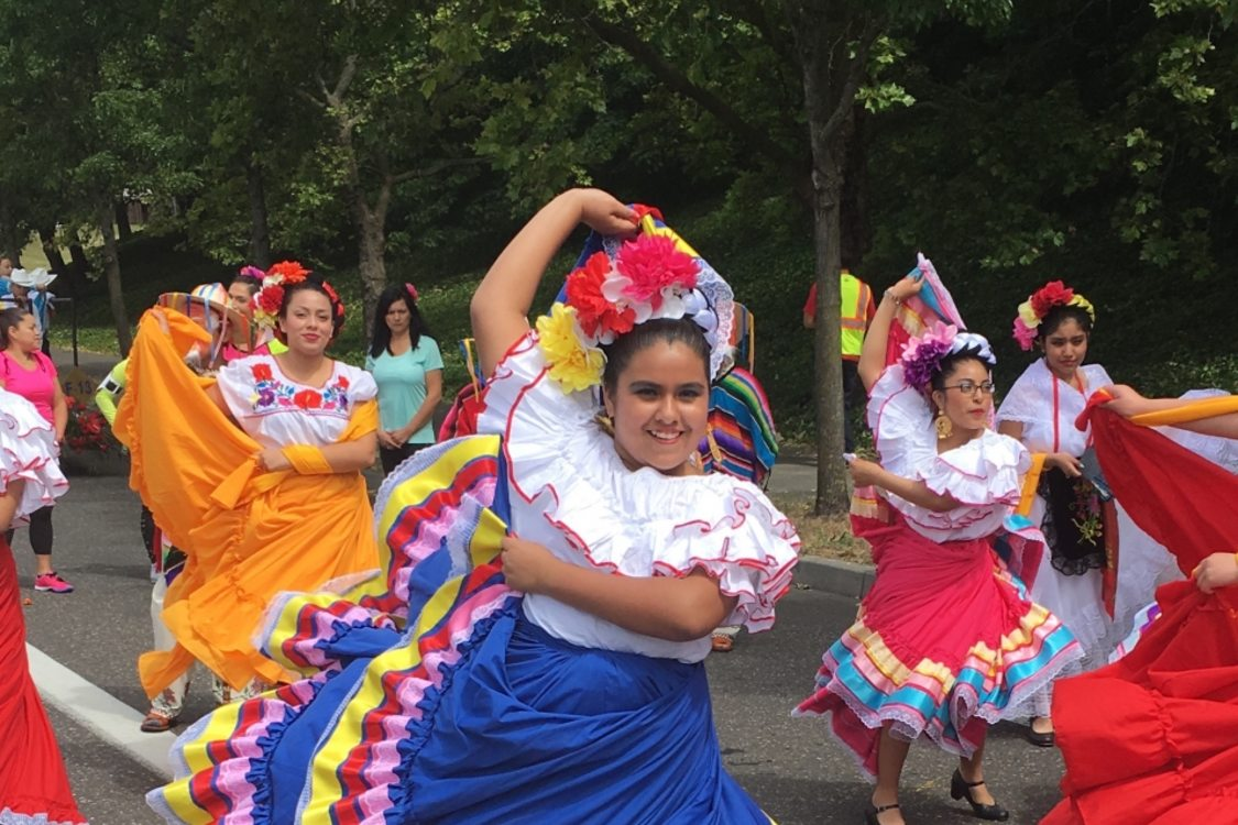 a troupe of young women in colorful dresses dancing down a street during the 2016 Rose Festival Parade