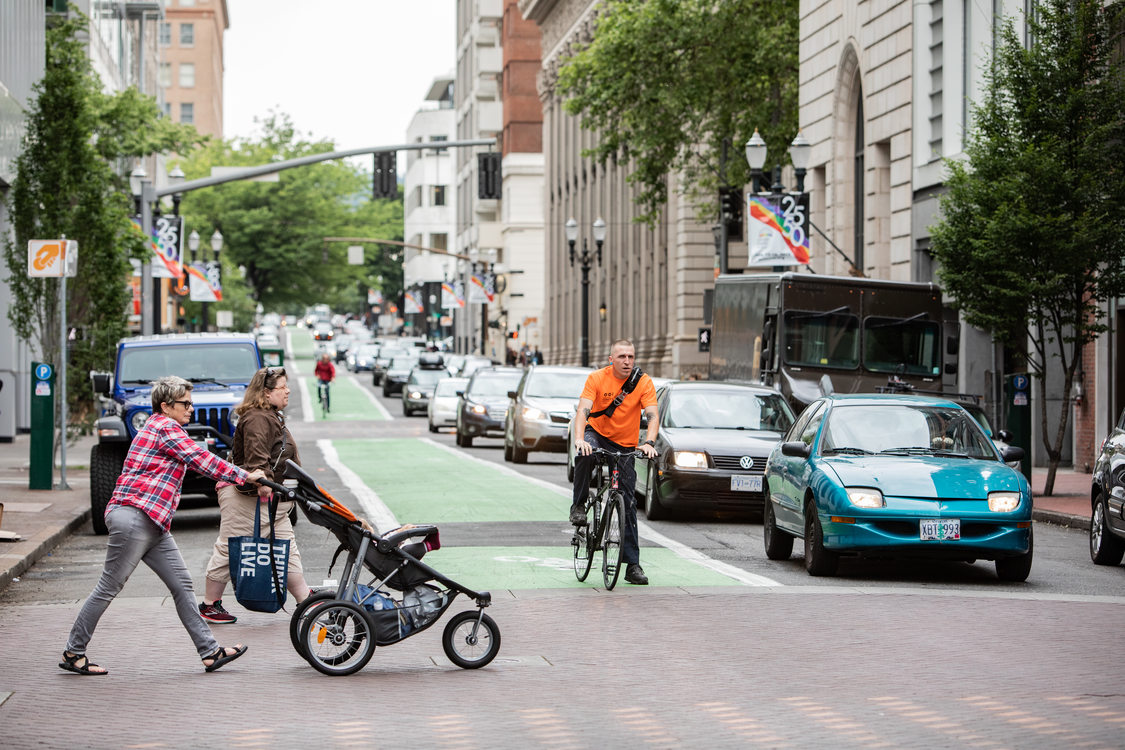 pedestrians cross a street in downtown Portland while a bicyclist and cars wait