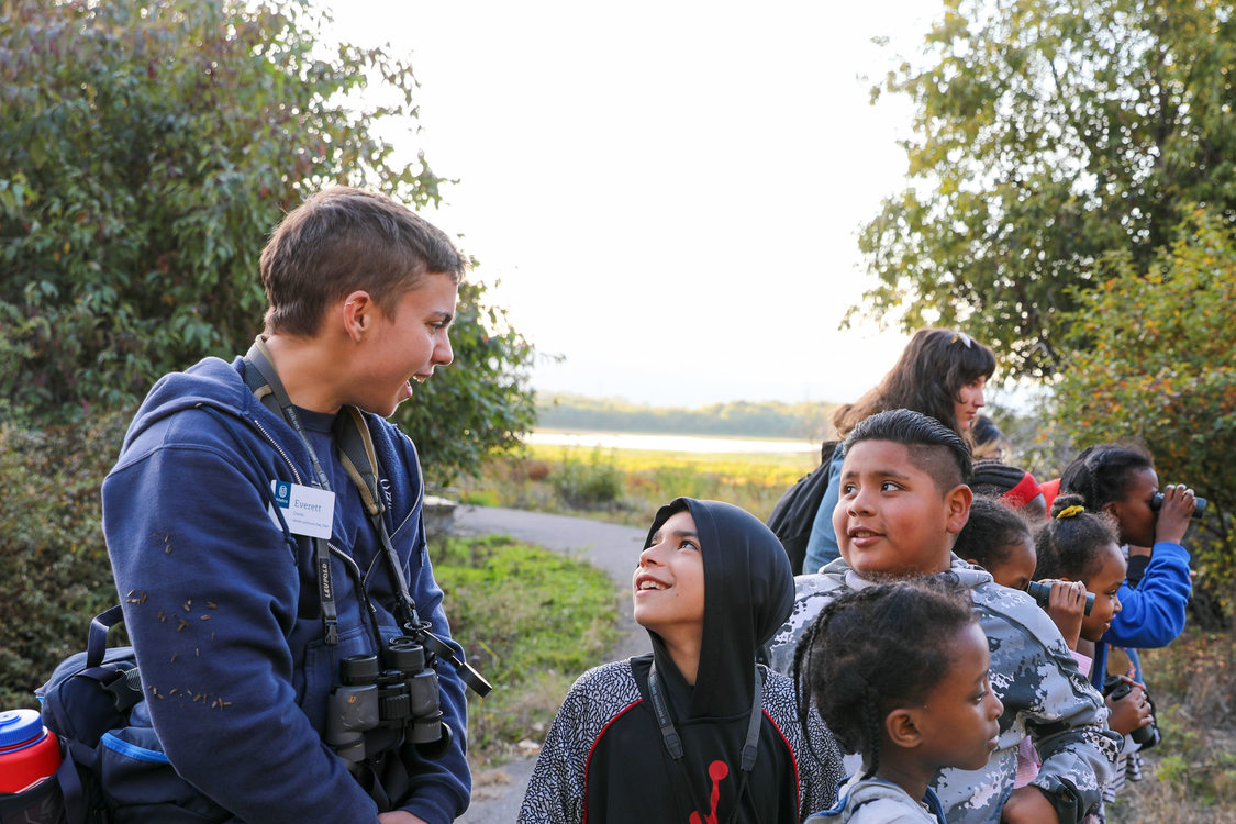 Naturalists speak with students in nature