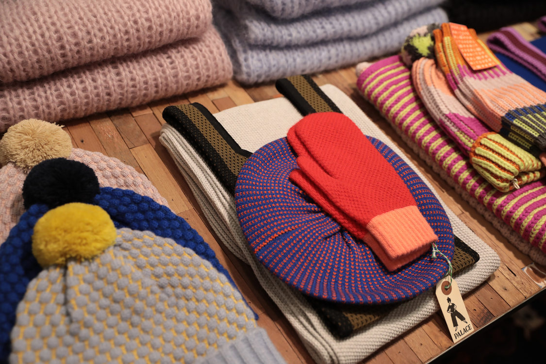 a selection of colorful  knit hats and mittens at a local shop