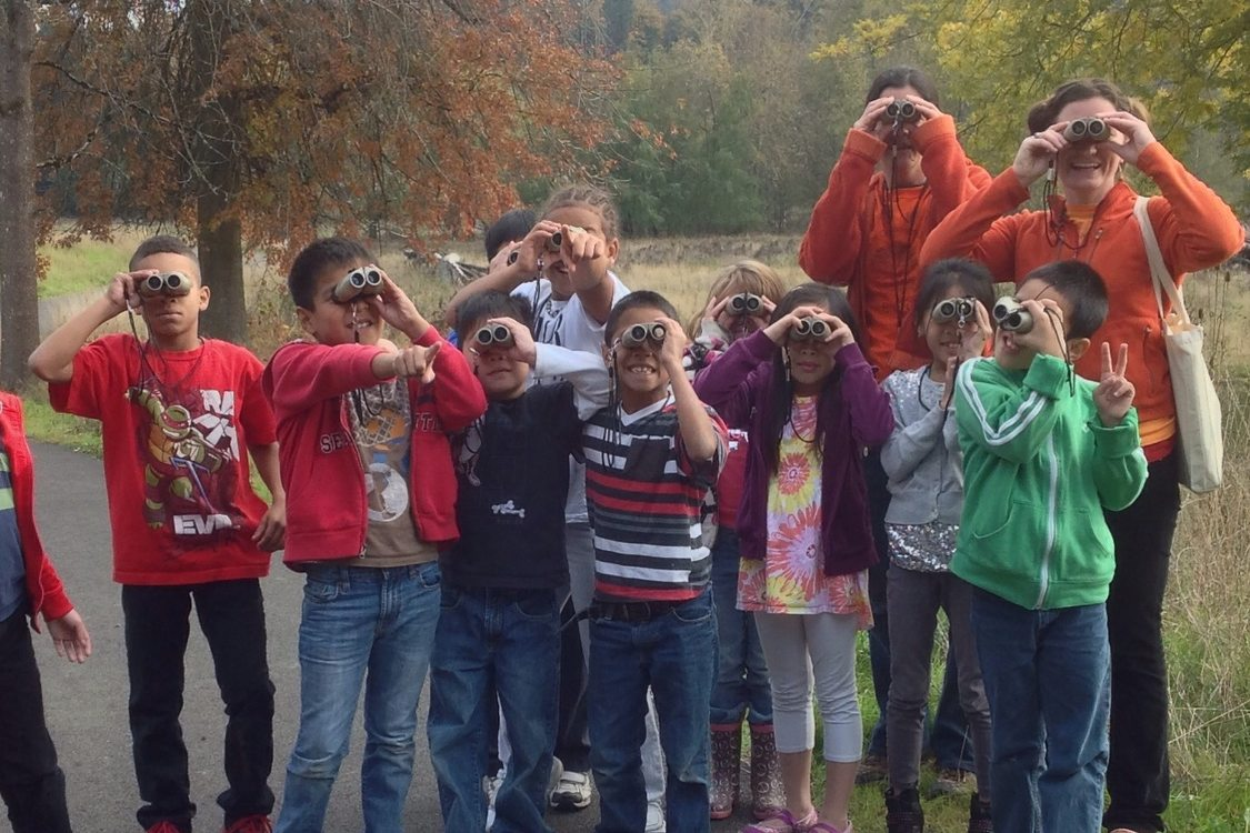 A group of about 8 children and two adults are facing the camera but looking through binoculars at something beyond the photographer with a field and trees in the background.