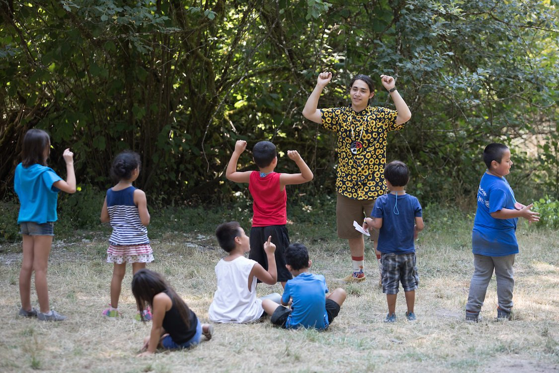 Eight young children with their backs to the camera are in a field with trees in the background focusing on an instructor who is holding their arms up. Two of the children are copying the gesture.