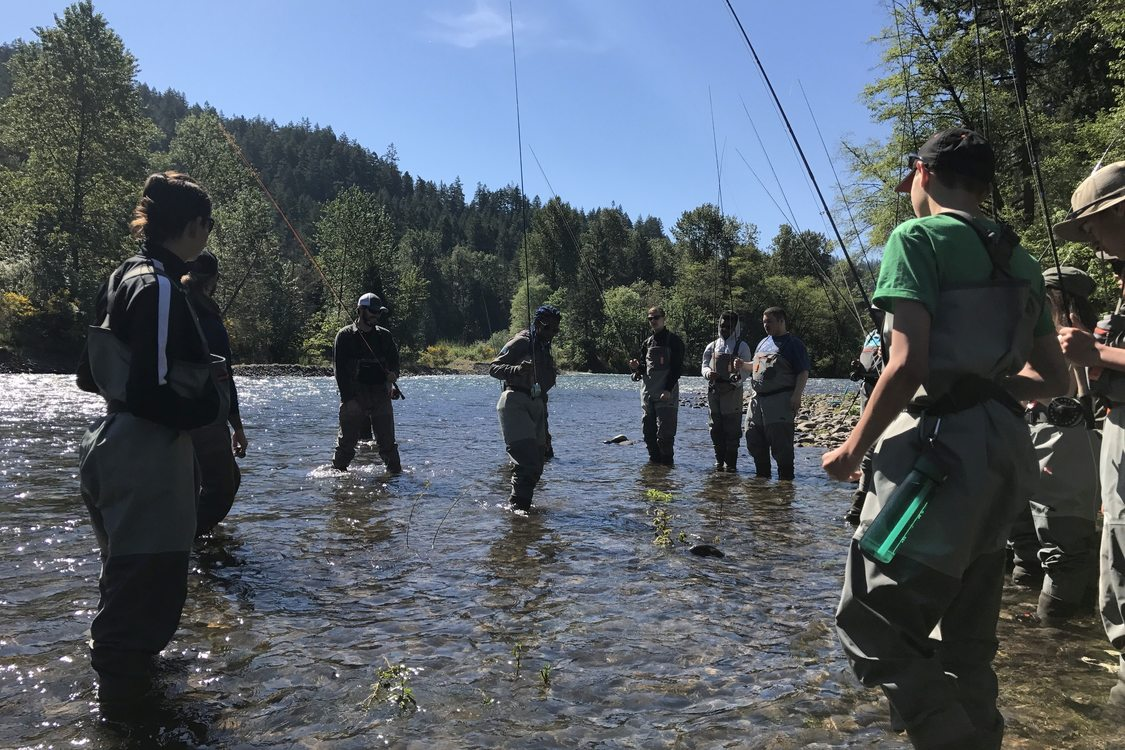 Ten youth in waders holding fly fishing poles stand calf deep in the river on a sunny day watching their instructor. There are green trees visible in the background.