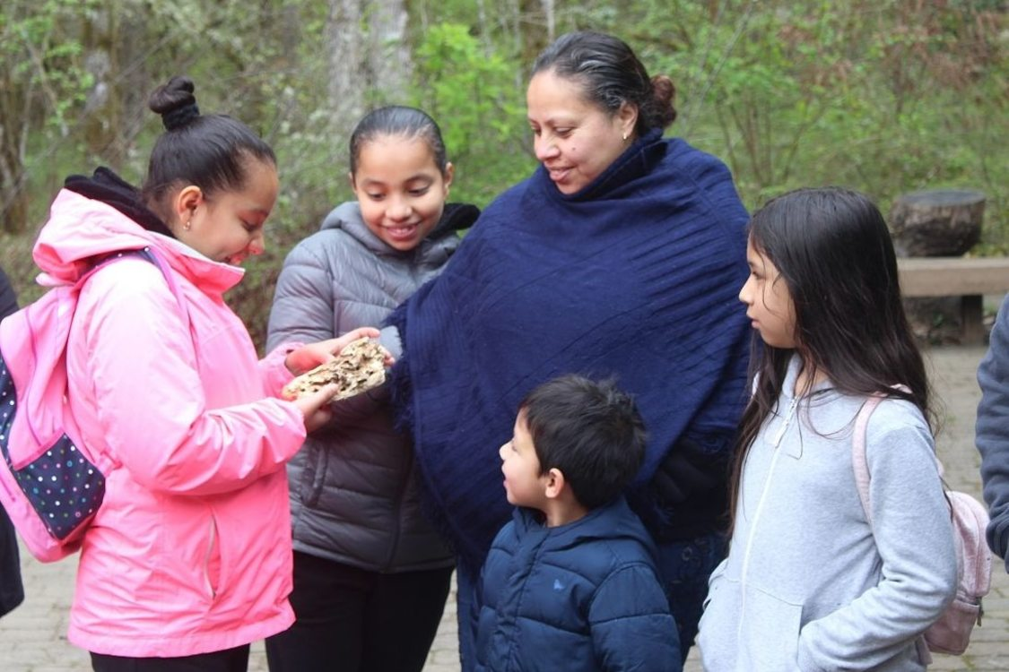 An adult stands surrounded by four children of various ages. One child is holding a piece of wood and the rest of the group is looking at it.