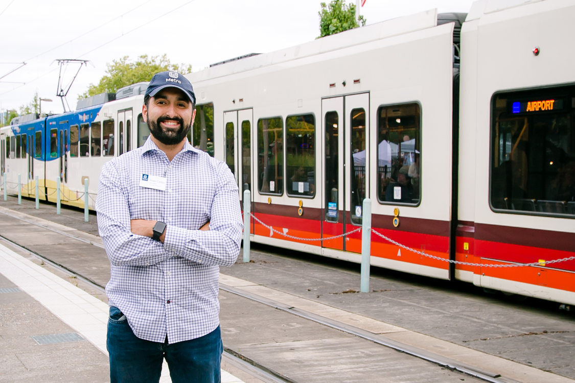 Metro Councilor Juan Carlos Gonzalez standing next to a MAX light rail train