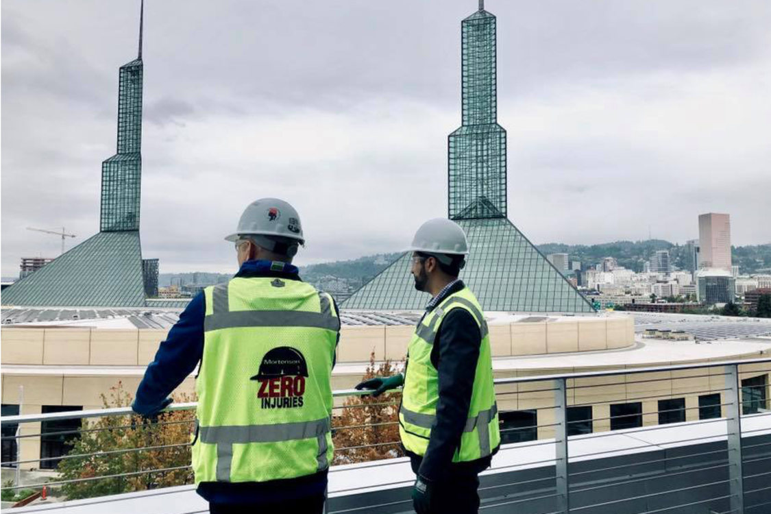 Metro Councilor Juan Carlos Gonzalez in a hard hat and construction vest overlooking the Oregon Convention Center from the top of the Hyatt Regency hotel