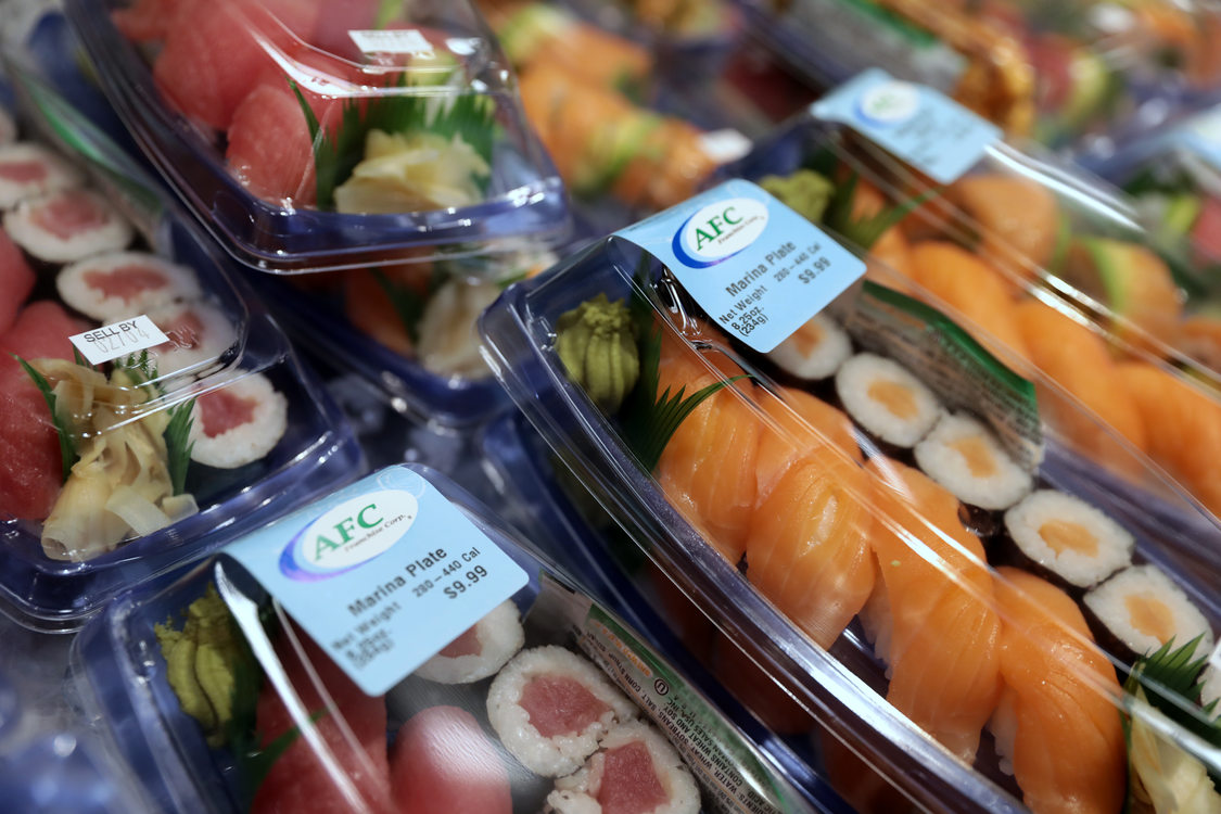 Grocery store deli section offering sushi in plastic take out containers
