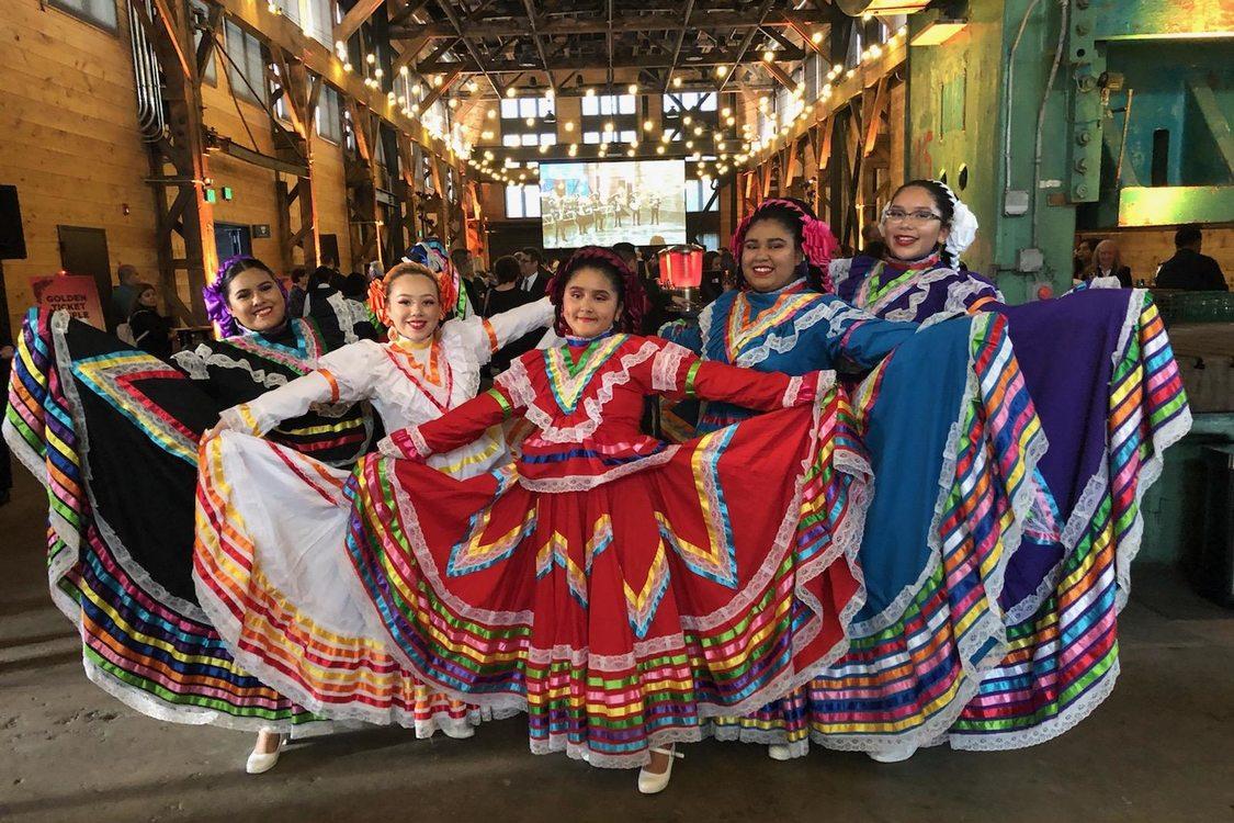 Chicas en sus vestidos tradicionales del baile folclórico muestran sus amplias faldas como abanicos.