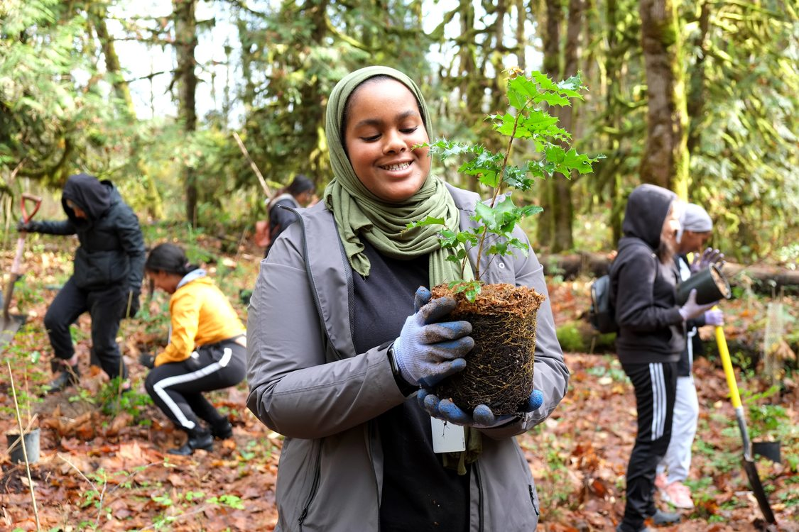 A young woman in hijab holds a tree as other teenagers plant trees at Oxbow Regional Park.