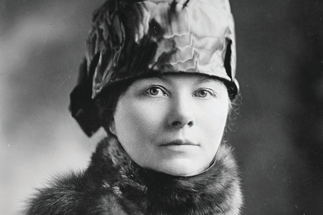 A white woman wearing a silk hat and fur scarf poses for a black-and-white portrait.