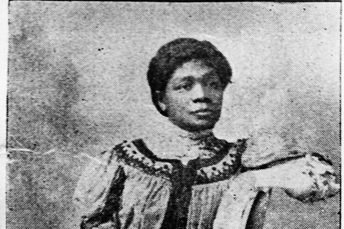 A sophisticated, lovely black woman wearing an embroidered dress and white gloves  poses for a black-and-white photograph