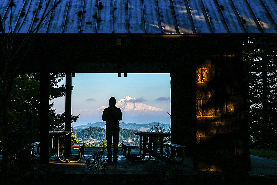 A person stands in the shadow of a picnic shelter while Mount Hood, covered in snow, rises in the horizon.