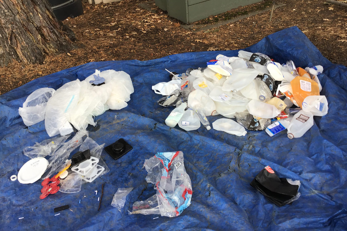 several piles of types of plastic laid out on a tarp for sorting and recycling