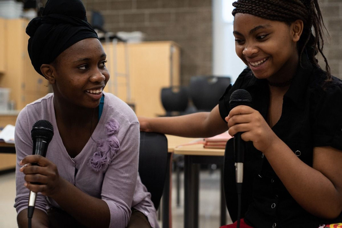 two women holding microphones and smiling in a community conversation at Ethos Music Center
