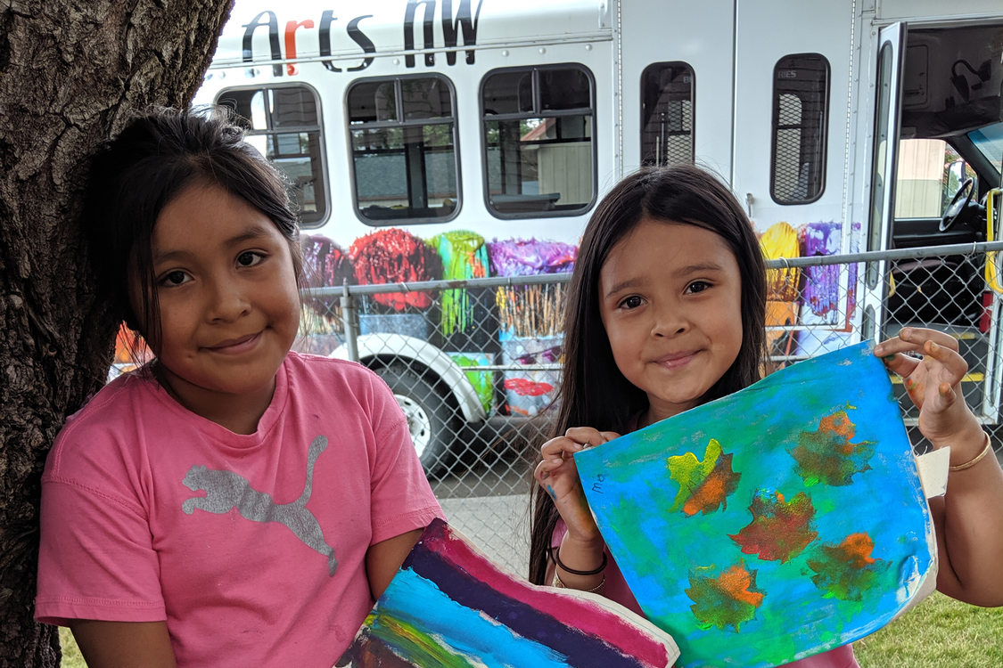 two young girls holding painted artwork they created in the Mobile Community Mural program from PlayEast