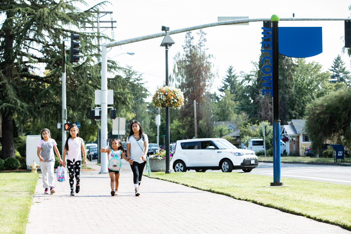 A woman and three children walk on a sidewalk, a car turning in the background