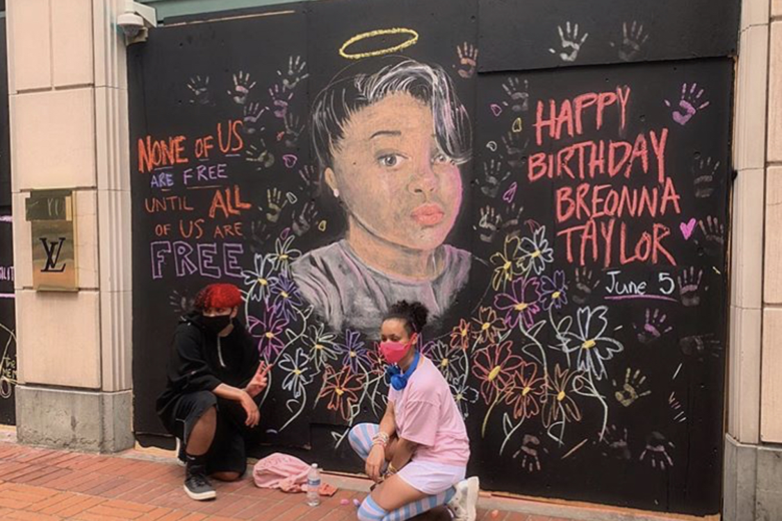 two teenagers pose in front of the mural they painted of Breonna Taylor