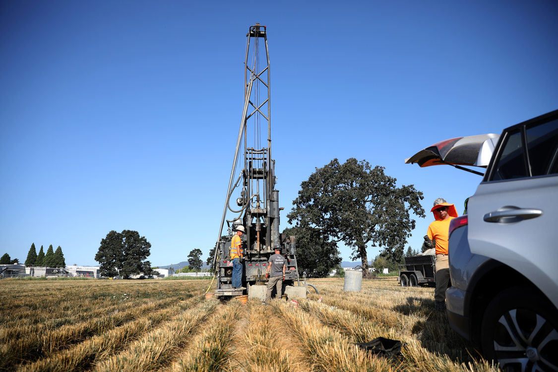 A small crew of there workers drill a 100-foot test hole into the ground of an open field.
