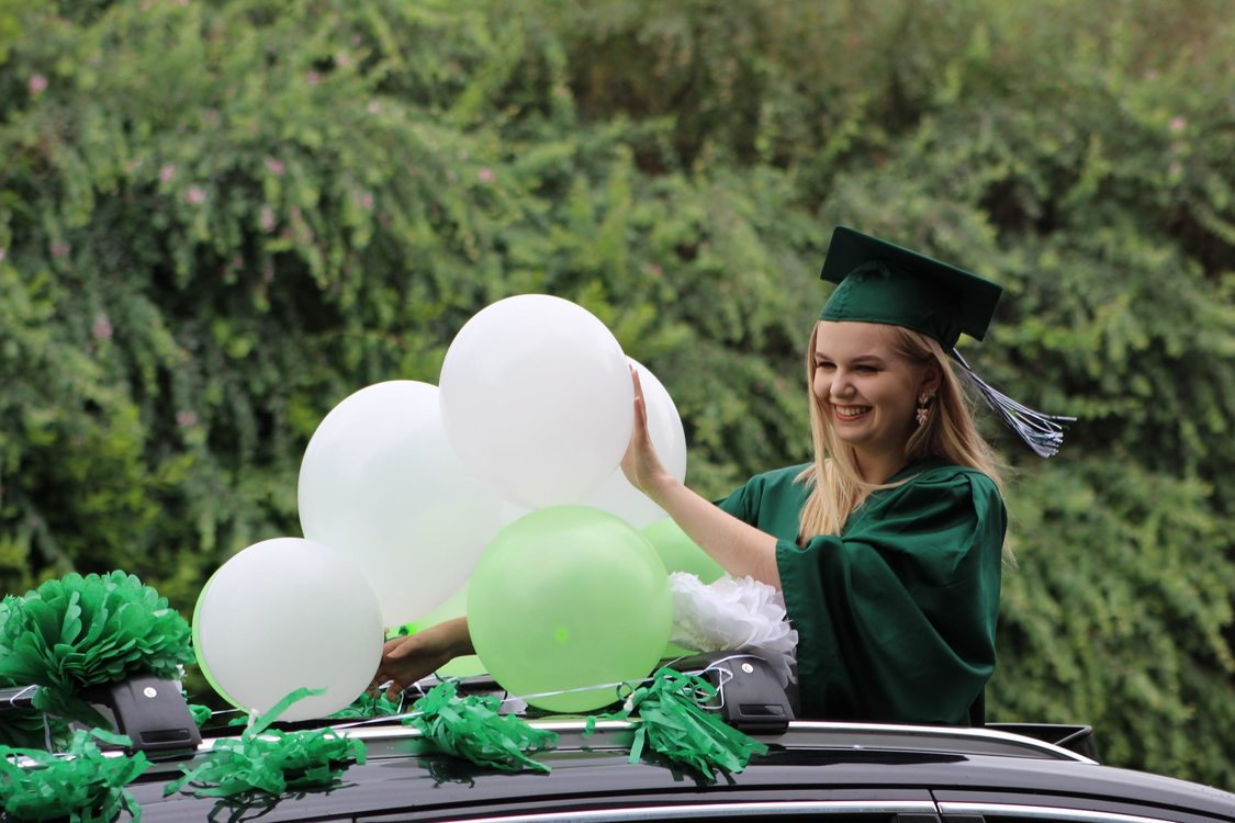a high school student, standing through a car's sunroof, adjusts balloons as she waves for photos during a drive-thru graduation ceremony June 8 at Wilson High School.