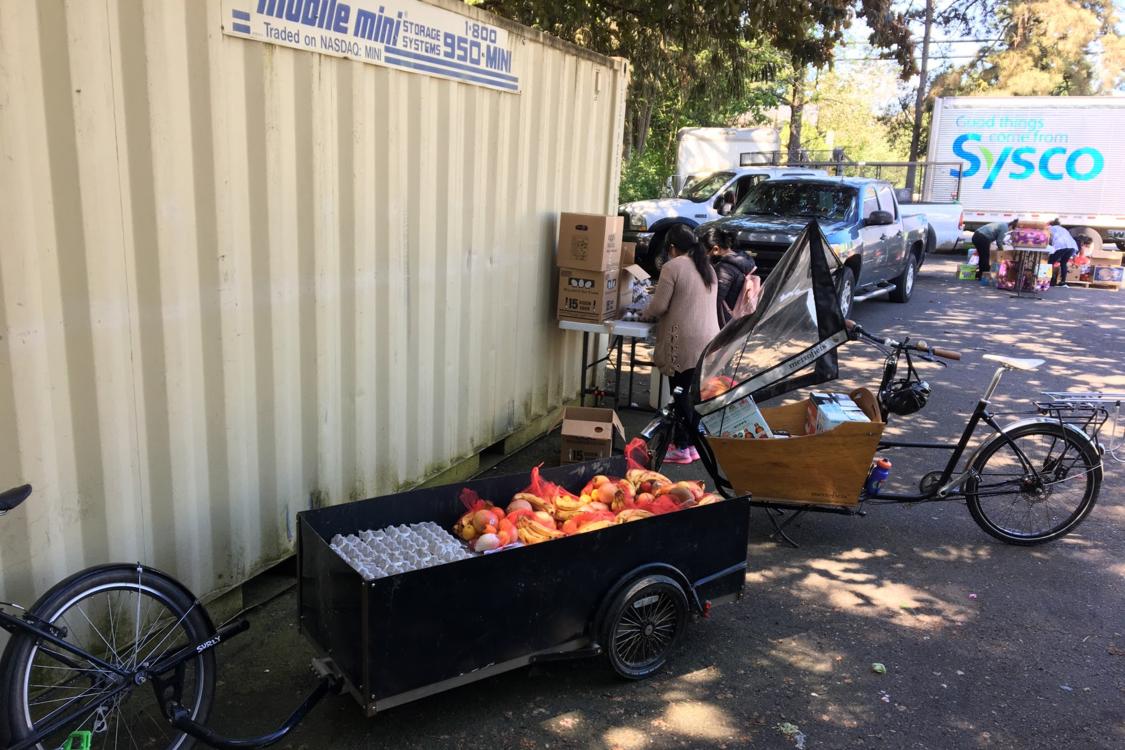 Volunteers preparing boxes of food in an outdoor setting