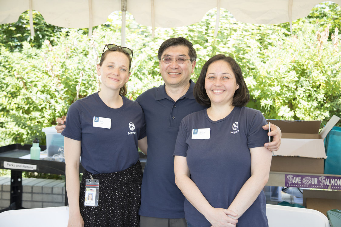 three people in navy blue shirts standing next to each other smiling