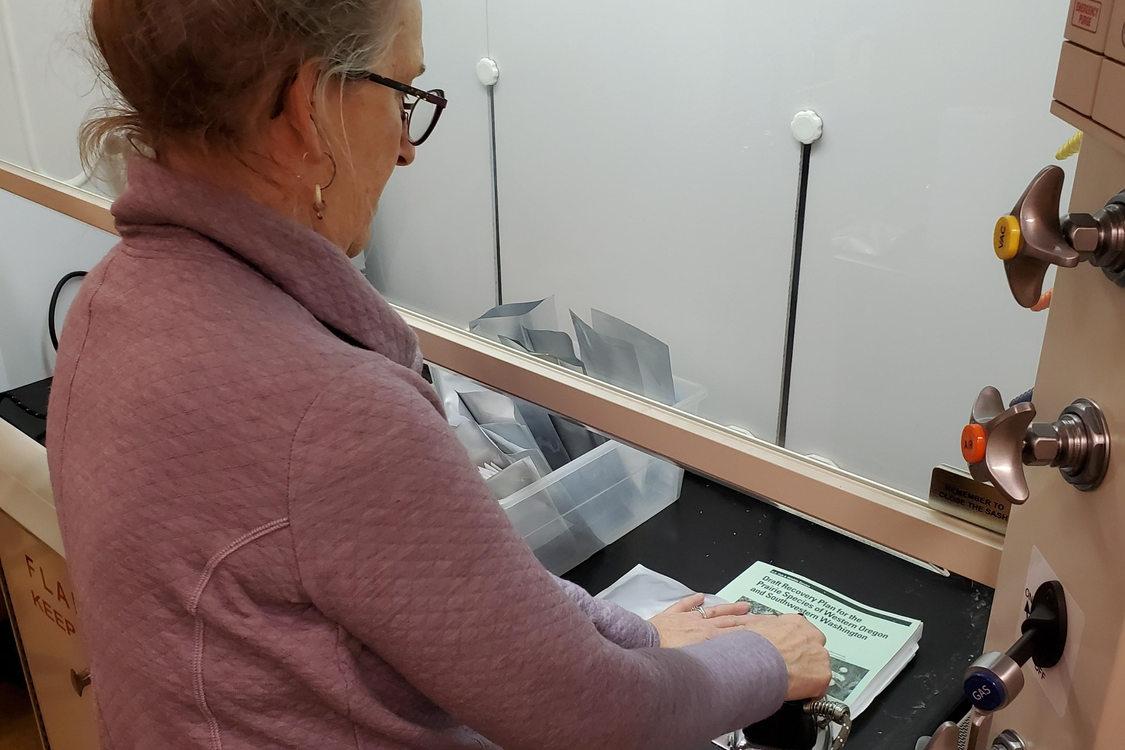 Marsha sealing seed envelopes at PSU's seed bank.