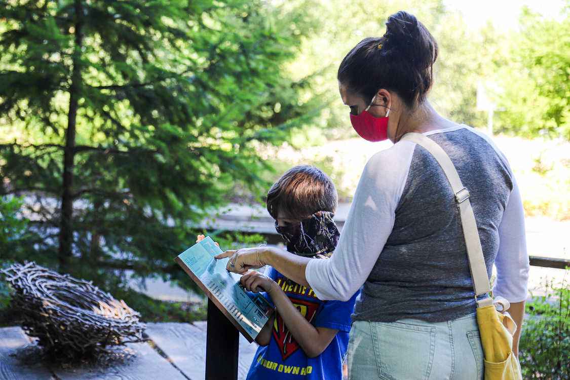 a woman and child wearing masks read an information sign in a Metro park