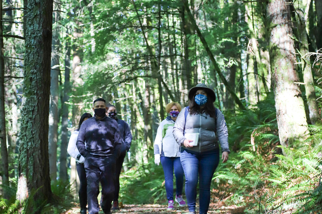 a group of people wearing masks walk along a shaded trail in a Metro park