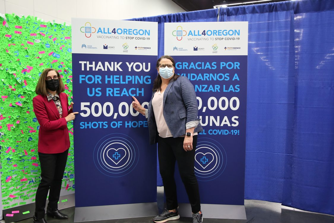 Governor Kate Brown and another woman wear masks and stand next to a banner for All4Oregon at the Oregon Convention Center mass COVID-19 vaccination site