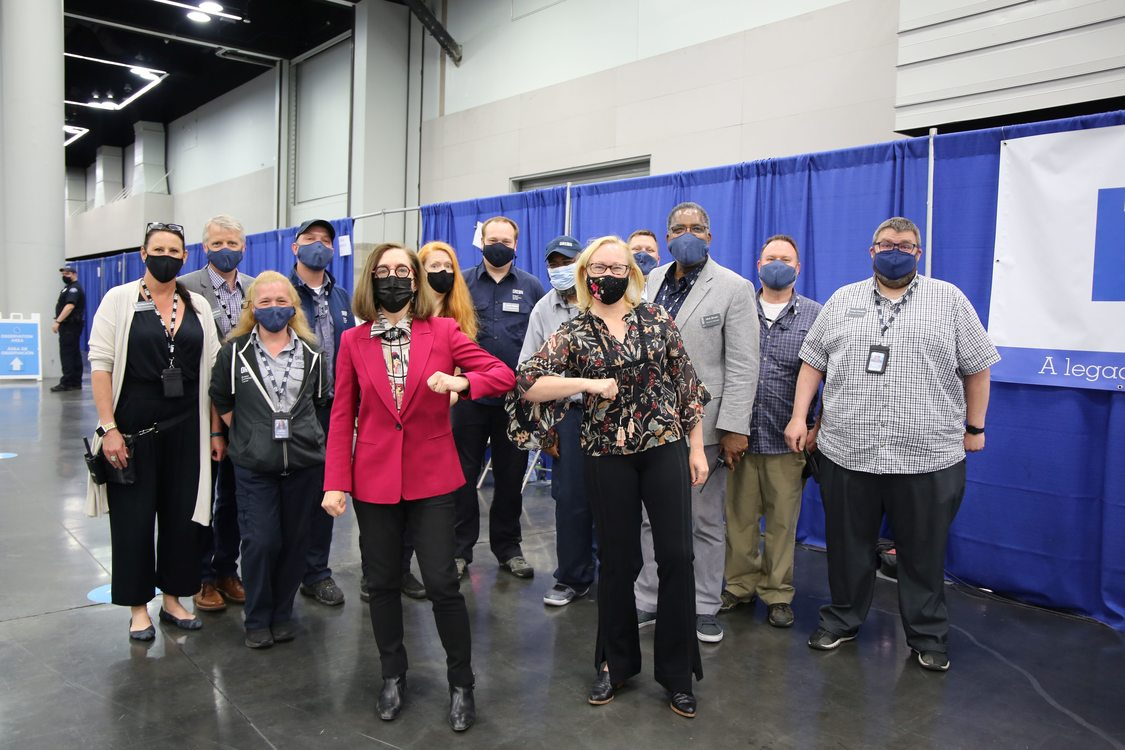 Governor Kate Brown and Metro Council President Lynn Peterson wear masks and stand with a crowd of masked staff and volunteers at the Oregon Convention Center mass COVID-19 vaccination site